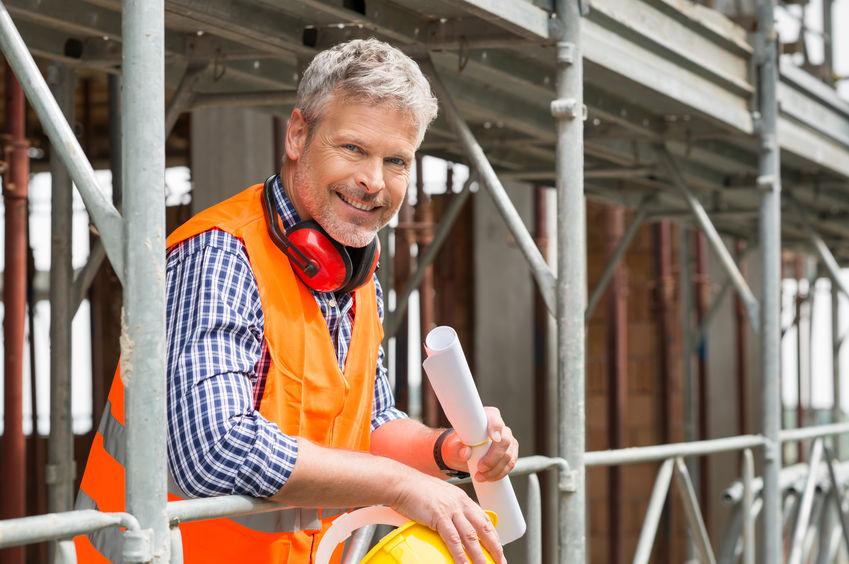 férfi építész mosolyog az építkezésen